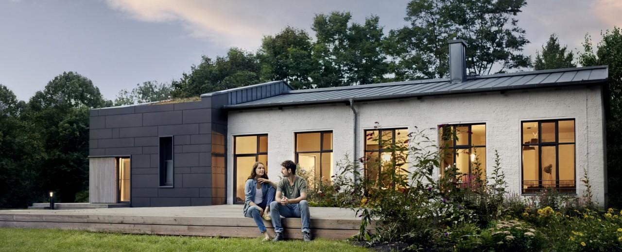 Junges Paar sitzt im Garten ihres modernen Hauses