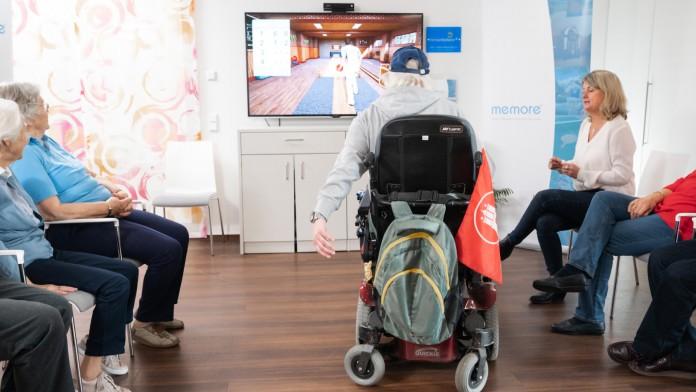 Im Altenheim spielt eine Seniorin im Rollstuhl auf der memoreCare-Konsole Kegeln