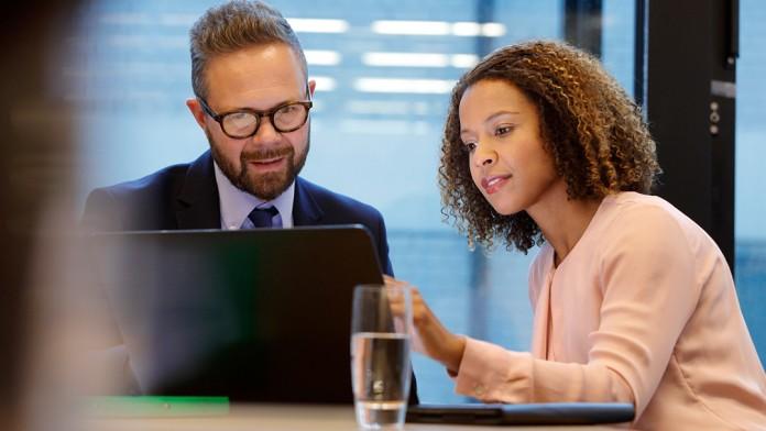 Ein Mann und eine Frau sitzen gemeinsam an einem Tisch und schauen auf einen Laptop.