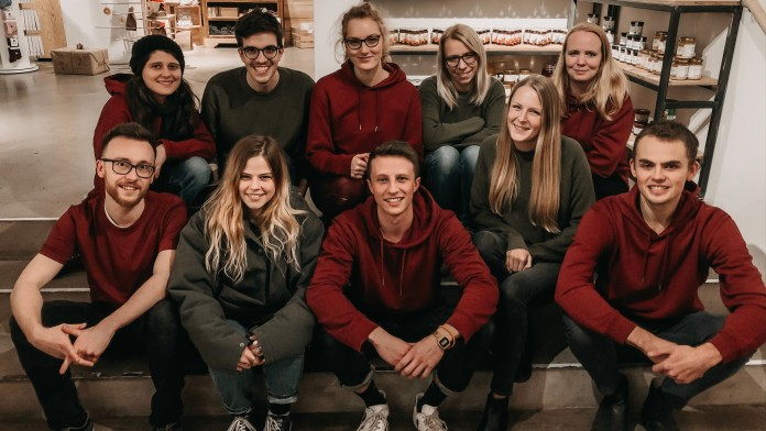 Eine Gruppe junger Menschen sitzt in Ihrem Geschäft für nachhaltige Kleidung und Unverpacktes.