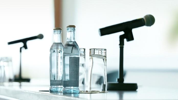 Rednerpult mit Mikrofon und Wasserflaschen