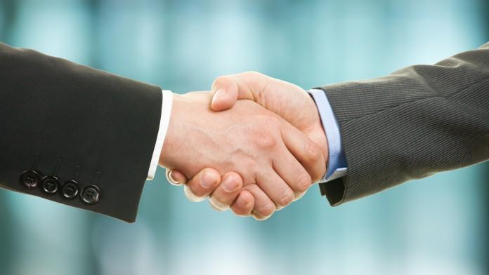 zwei Hände treffen sich zu einem Handschlag