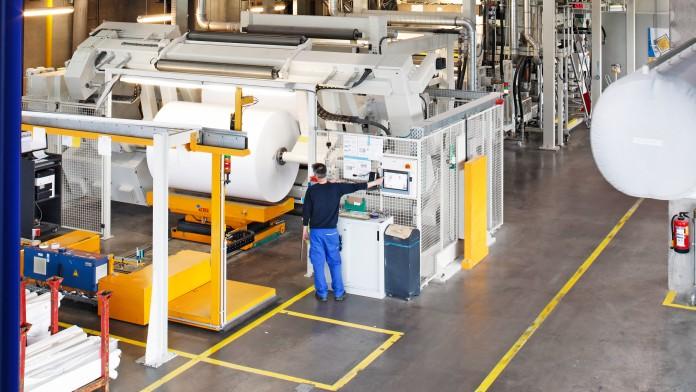 Ein Mitarbeiter bedient in der Produktionshalle eine Maschine