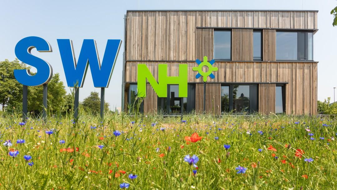 Energieeffizientes Verwaltungsgebäude der Stadtwerke Neustadt mit Wiese davor