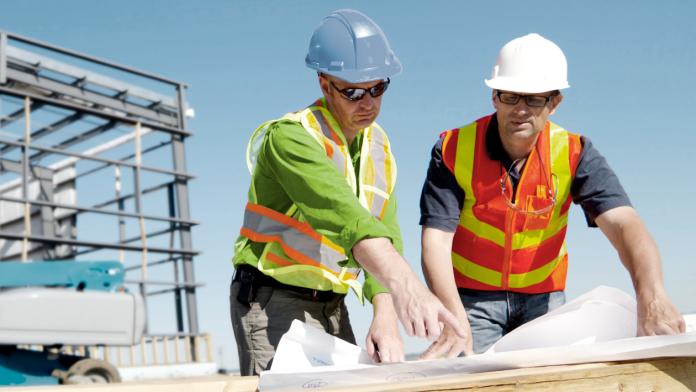 Zwei Architekten auf einer Baustelle blicken auf eine Bauzeichnung