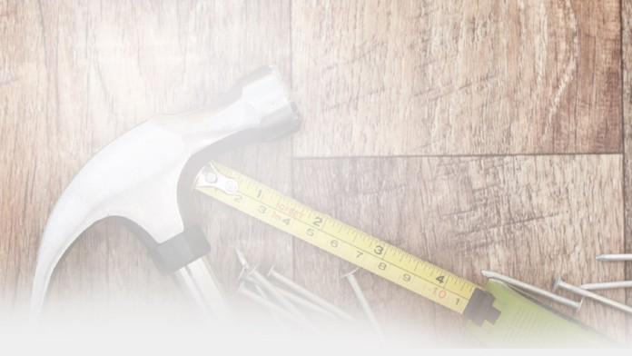 Zimmermannshammer und Nägel auf einem Holztisch