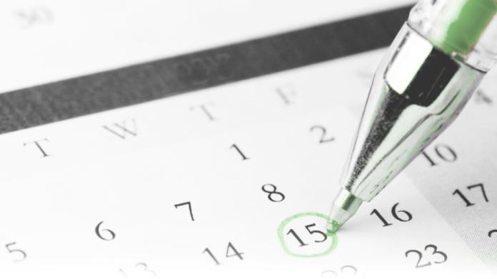 Mit einem Kugeschreiber wird ein Datum in einem Kalender angekreuzt
