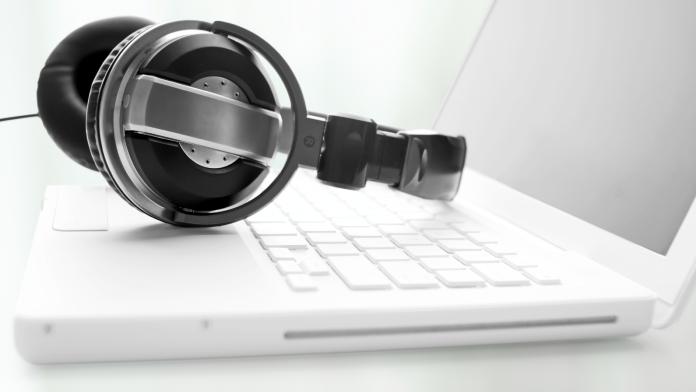 Kopfhörer liegen auf der Tastatur eines Laptops