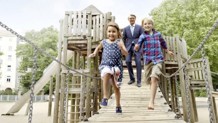 Zwei Kinder und ein Mann auf einem Klettergerüst eines Spielplatzes