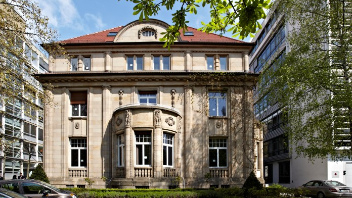 Außenansicht der Villa 102, ein neoklassizistisches Gebäude. Im Vordergrund ist ein grüner Rasen. Links und rechts sind Bürogebäude.