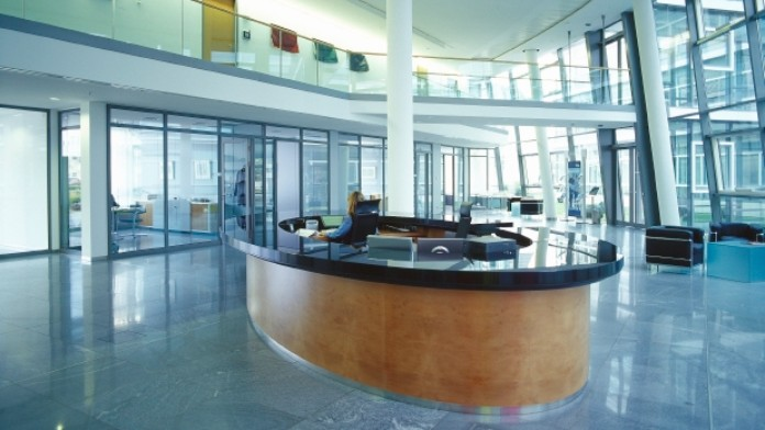 Innenansicht des Empfangsbereichs der KfW-Niederlassung Bonn. Ein ovaler Empfangstresen mittig, im Hintergrund Beratungsräume mit Glasfenstern.