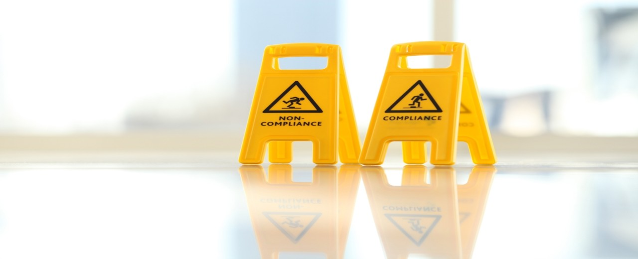 """Warnpoller mit der Aufschrift """"Compliance"""" und """"Non-Compliance"""""""