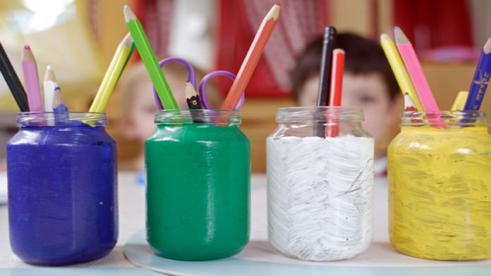 Buntstifte in Gläsern in einer Kindertagesstätte, im Hintergrund sind Kinder zu sehen.